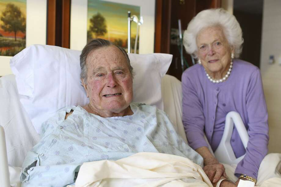 Former President George H.W. Bush recovers last week in his bed at Houston Methodist Hospital with his wife, Barbara, at his side. The 92-year-old received treatment for pneumonia. Photo: Jim McGrath, Associated Press
