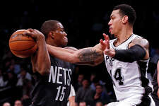 San Antonio Spurs guard Danny Green (14) knocks the ball away from Brooklyn Nets guard Isaiah Whitehead (15) during the first half of an NBA basketball game, Monday, Jan. 23, 2017, in New York. (AP Photo/Adam Hunger)