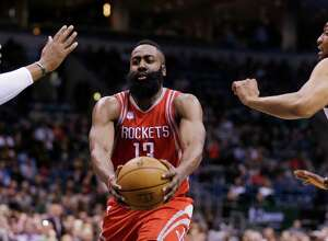 Houston Rockets' James Harden (13) drives between Milwaukee Bucks' Greg Monroe, right, and Jabari Parker during the first half of an NBA basketball game, Monday, Jan. 23, 2017, in Milwaukee. (AP Photo/Jeffrey Phelps)