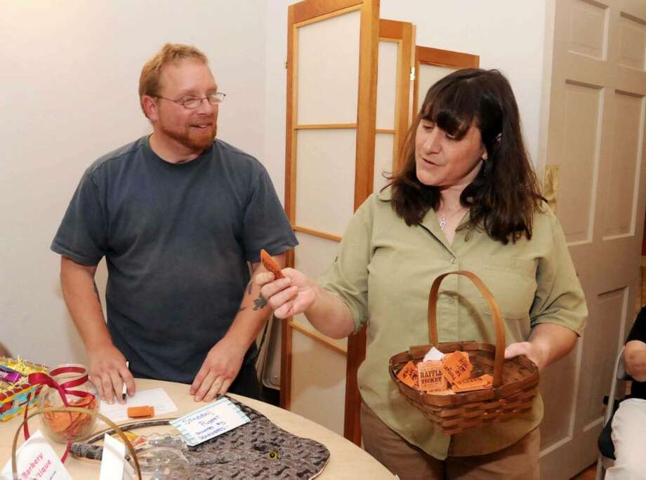 Wayne McCarthy, left, helps Debbie Corcione with the raffle drawing at the Wildlife-line baby shower on Sunday, May 23, 2010. Both are from Sherman. Photo: Lisa Weir / The News-Times Freelance