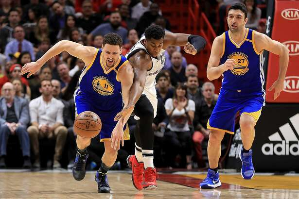 MIAMI, FL - JANUARY 23: Klay Thompson #11 of the Golden State Warriors and Hassan Whiteside #21 of the Miami Heat fight for a loose ball during a game ` at American Airlines Arena on January 23, 2017 in Miami, Florida. NOTE TO USER: User expressly acknowledges and agrees that, by downloading and or using this photograph, User is consenting to the terms and conditions of the Getty Images License Agreement.  (Photo by Mike Ehrmann/Getty Images)