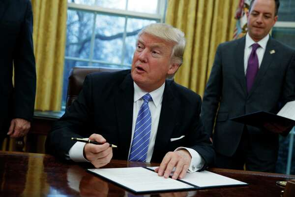 President Donald Trump signs an executive order to withdraw the U.S. from the 12-nation Trans-Pacific Partnership trade pact agreed to under the Obama administration, Monday, Jan. 23, 2017, in the Oval Office of the White House in Washington. (AP Photo/Evan Vucci) ORG XMIT: DCEV112
