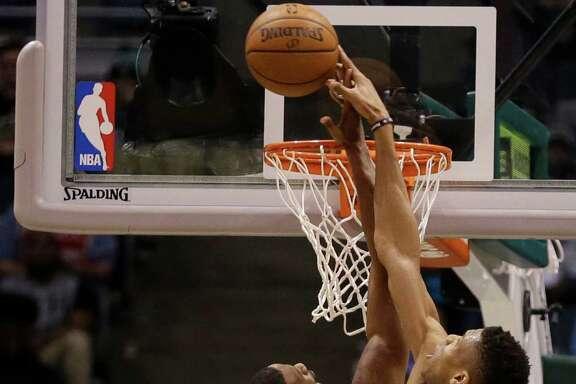 Milwaukee Bucks' Giannis Antetokounmpo, right, blocks the shot by Houston Rockets' Trevor Ariza during the second half of an NBA basketball game Monday, Jan. 23, 2017, in Milwaukee. (AP Photo/Jeffrey Phelps)