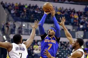 New York Knicks forward Carmelo Anthony (7) shoots between Indiana Pacers center Al Jefferson (7) and center Myles Turner (33) during the first half of an NBA basketball game in Indianapolis, Monday, Jan. 23, 2017. (AP Photo/Michael Conroy) ORG XMIT: NAF104