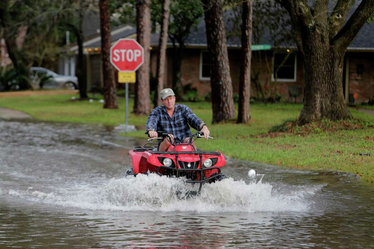 Mark Taylor crosses N. Braeswood Blvd. at Braewick on a four-wheeler past several flooded vehicles, Tuesday, Jan. 17, 2017, in Houston. Taylor's house around the corner just north of Brays Bayou has flooded in the two previous significant floods, but no water entered his house this time. ( Mark Mulligan / Houston Chronicle )