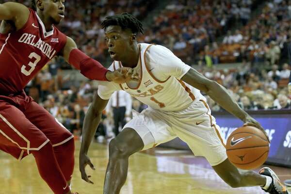 b254255b08c10e 1of2Texas guard Andrew Jones (1) looks for room around Oklahoma guard  Christian James (3) during first half action Monday Jan. 23