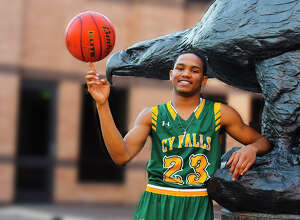 Cy Falls junior guard Nigel Hawkins spins a basketball in front of Cy Falls High School, aside a statue of the school's mascot, an eagle. Hawkins, leading the district in scoring at 21.7 points per game, believes he has what it takes to earn District MVP honors, and unless Cy Falls (6-0) loses a district contest, it is hard to argue against his case.