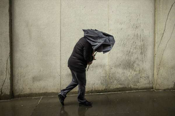 A woman walks against heavy wind in downtown New York, Monday, Jan. 23, 2017. Millions of people from the mid-Atlantic through New England were being advised to hunker down as a nor'easter moves up the coast. (AP Photo/Andres Kudacki)