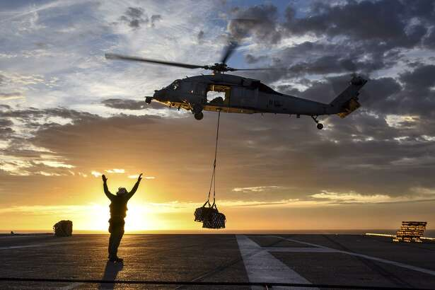 A sailor directs a Sikorsky MH-60S Seahawk helicopter to lower supplies onto the flight deck of the aircraft carrier USS Carl Vinson during a vertical replenishment with the fleet replenishment oiler USNS Yukon in the Pacific Ocean, Jan. 7, 2017. (U.S. Navy photo by Specialist 2nd Class Sean M. Castellano/Released)