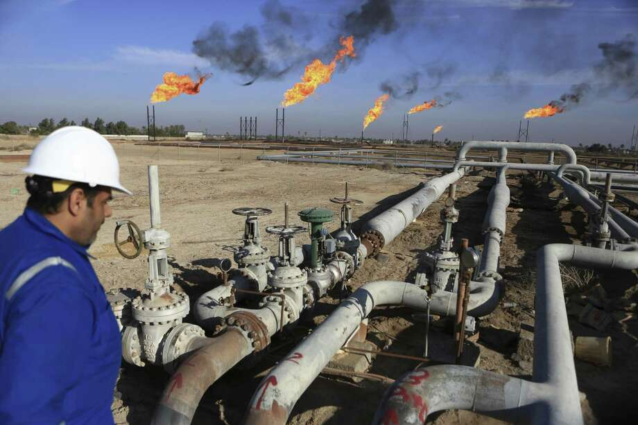 An Iraqi worker worker prepares to operate valves in Nihran Bin Omar field north of Basra, 340 miles southeast of Baghdad. Iraq has trimmed supply by 180,000 barrels a day and will cut a further 30,000-a-day by the end of the month, Oil Minister Jabbar al-Luaibi said. Photo: Nabil Al-Jurani /Associated Press / Copyright 2017 The Associated Press. All rights reserved.