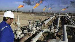 An Iraqi worker worker prepares to operate valves in Nihran Bin Omar field north of Basra, 340 miles southeast of Baghdad. Iraq has trimmed supply by 180,000 barrels a day and will cut a further 30,000-a-day by the end of the month, Oil Minister Jabbar al-Luaibi said.
