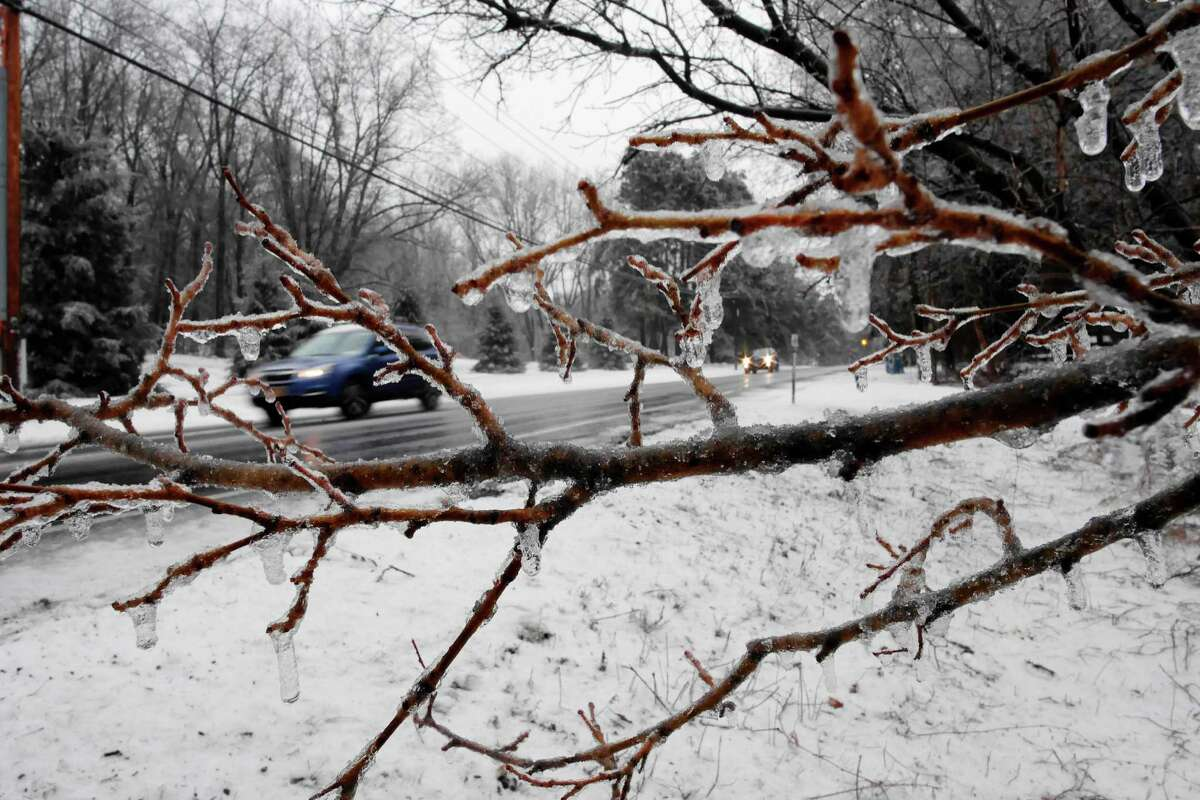 Ice covers the branches of trees as cars travel by on Old Niskayuna Road in Colonie, N.Y. (Paul Buckowski / Times Union archive)