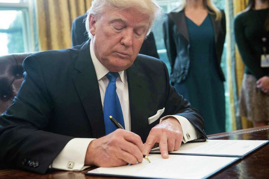 President Donald Trump signs an executive order Tuesday in the Oval Office. Trump signed executive orders Tuesday reviving the construction of two controversial oil pipelines, but said the projects would be subject to renegotiation. Photo: Nicholas Kamm /AFP /Getty Images / AFP or licensors