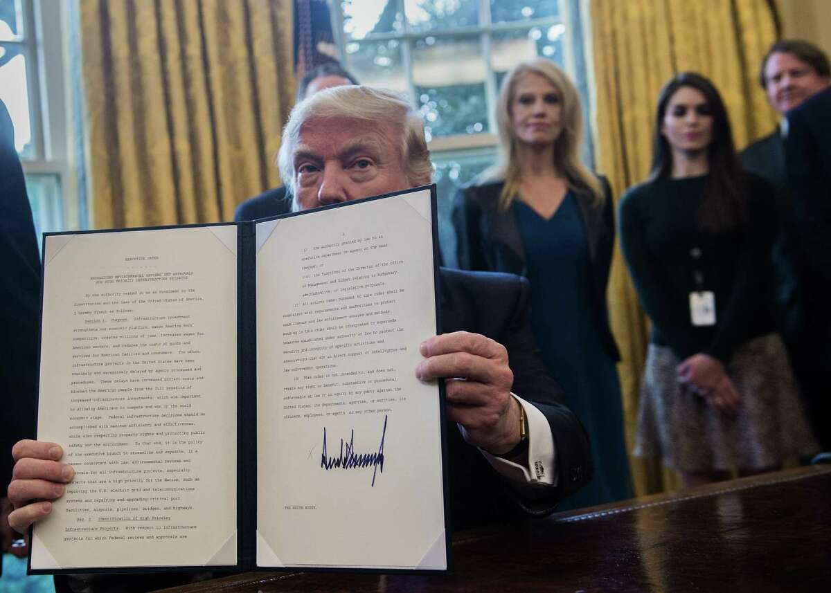 President Donald Trump shows his signature on an executive order Tuesday. Trump revived the Keystone XL pipeline, which stirred years of debate over the balance between the nation's energy needs and efforts to stem climate change. He also cleared the way for approval of the Dakota Access pipeline in North Dakota.