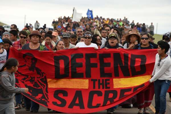 (FILES) This file photo taken on September 04, 2016 shows  Native Americans marching to a sacred burial ground, disturbed by bulldozers building the Dakota Access Pipeline (DAPL), near the encampment where hundreds of people have gathered to join the Standing Rock Sioux Tribe's protest of the oil pipeline that is slated to cross the Missouri River nearby, September 4, 2016 near Cannon Ball, North Dakota. The tribe's attempt for a temporary injunction to halt construction of the  pipeline near their reservation was denied on September 9, 2016, by US District Judge James Boasberg.  / AFP PHOTO / Robyn BECKROBYN BECK/AFP/Getty Images