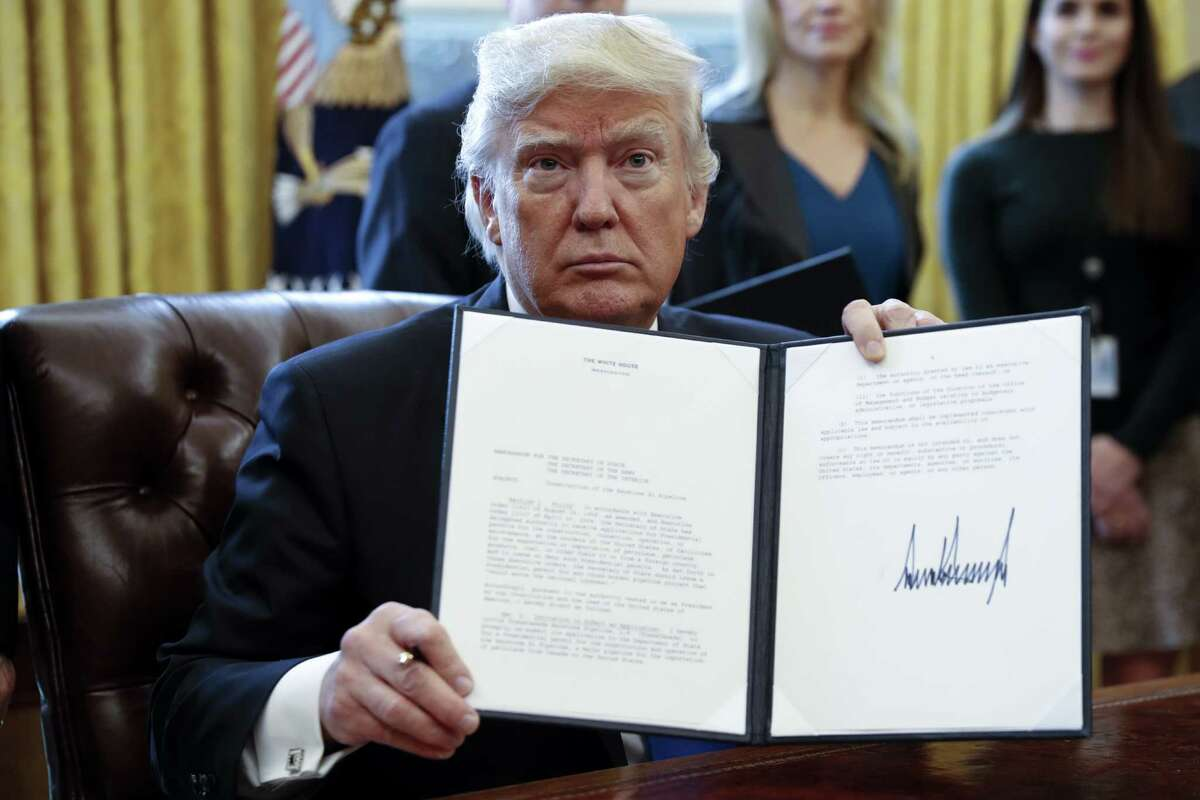 US President Donald Trump displays one of five executive orders he signed related to the oil pipeline industry for a photograph in the Oval Office of the White House in Washington, D.C., U.S., Tuesday, Jan. 24, 2017. Trump took steps to advance construction of the Keystone XL and Dakota Access oil pipelines while foreshadowing a