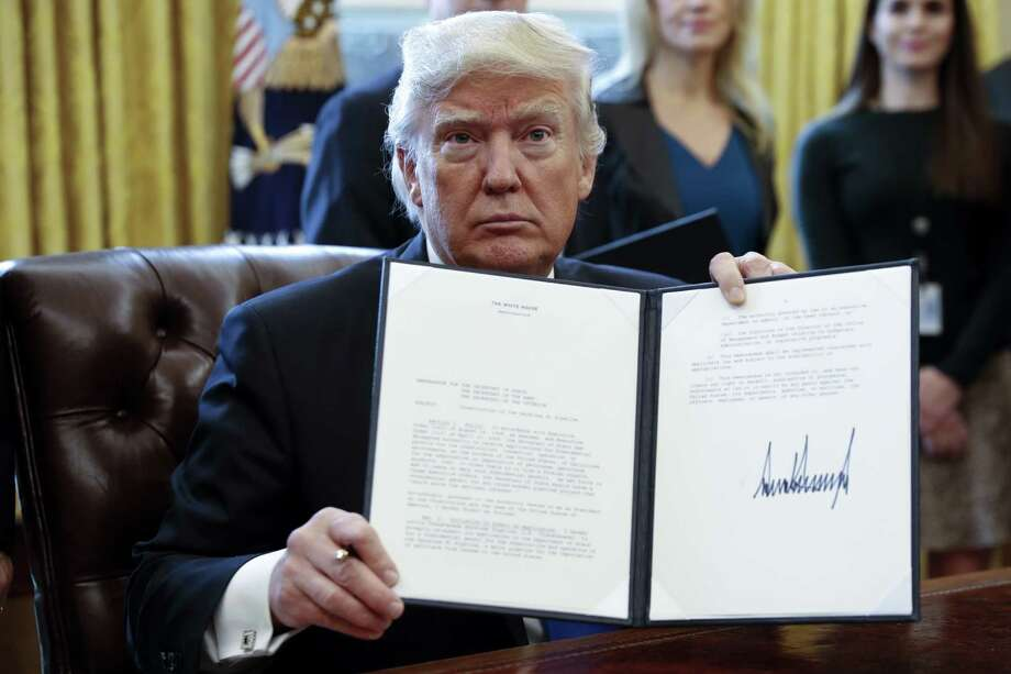 "US President Donald Trump displays one of five executive orders he signed related to the oil pipeline industry for a photograph in the Oval Office of the White House in Washington, D.C., U.S., Tuesday, Jan. 24, 2017. Trump took steps to advance construction of the Keystone XL and Dakota Access oil pipelines while foreshadowing a ""renegotiation"" of terms and insisting that developers use U.S. steel. Photographer: Shawn Thew/Pool via Bloomberg Photo: Shawn Thew / © 2017 Bloomberg Finance LP"