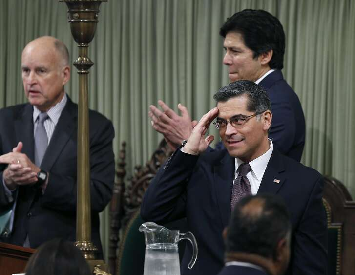 Xavier Becerra salutes lawmakers after he's sworn-in as attorney general by Gov. Jerry Brown before the governor's State of the State address at the Capitol in Sacramento, Calif. on Tuesday, Jan. 24, 2017.