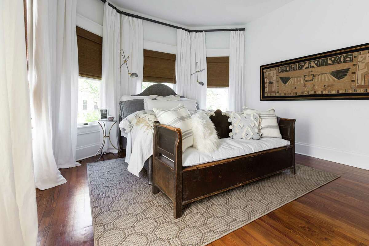 An Egyptian tapestry and Moroccan wedding blankets create an eclectic vibe in the master bedroom. Woodall and Crabtree used Audrey Tehauno and Jana Erwin from Nest Design Group to fill their home with a mix of new, vintage and antique decor.