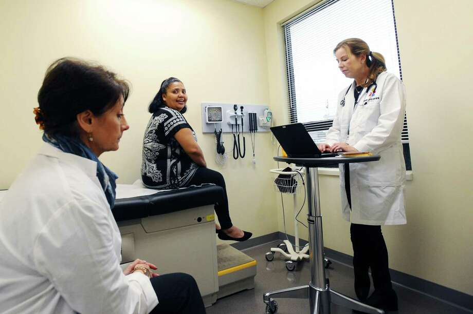 Sonia Godinez, center, smiles as she talks with Dr. Marcie Molloy, right, and interpreter Ana Lilienfeld during a check-up inside the Americares free clinic on Shippan Ave. in Stamford, Conn. on Tuesday, Jan. 24, 2017. Photo: Michael Cummo / Hearst Connecticut Media / Stamford Advocate