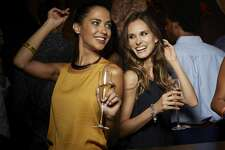 Cheerful female friends dancing while having champagne in nightclub