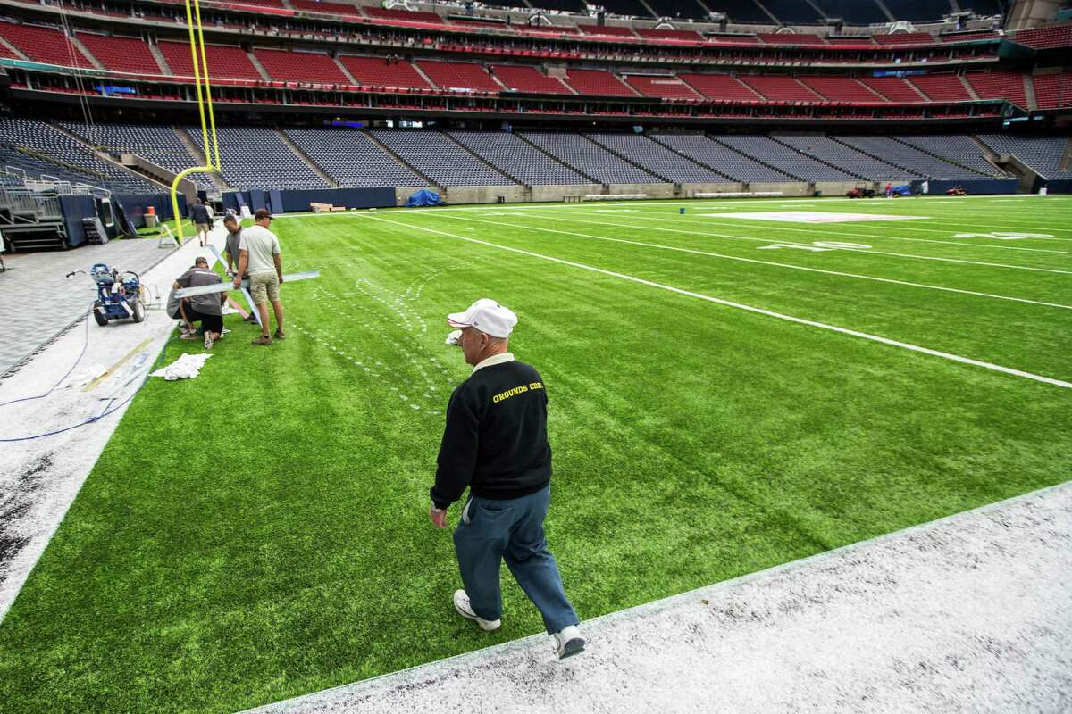 Groundskeeper George Toma walks onto the field as the turf is prepared for painting as NRG Stadium is prepared for Super Bowl LI on Tuesday, Jan. 24, 2017, in Houston. The New England Patriots play the Atlanta Falcons on February 5, for the NFL title.