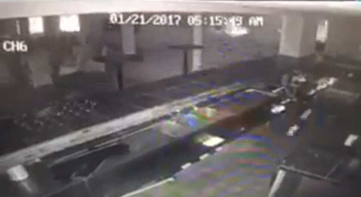 A screenshot from the surveillance video shows the wave crashing through the window.