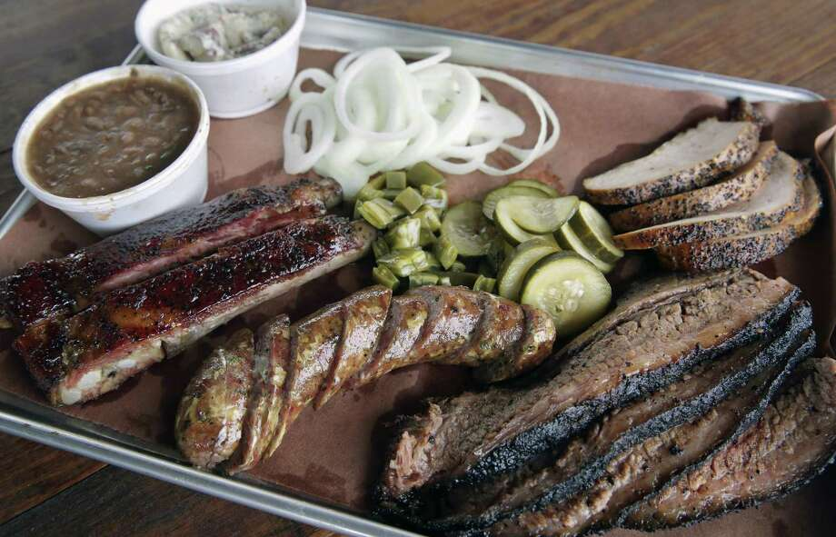 Ribs, sausage, brisket and turkey with pickles, onions cactus, beans and potato salad at 2M Smokehouse. Photo: Tom Reel /San Antonio Express-News / 2017 SAN ANTONIO EXPRESS-NEWS