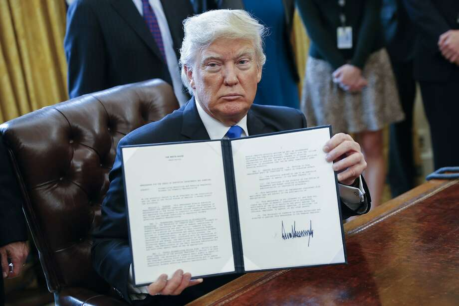 "US President Donald Trump displays one of five executive orders related to the oil pipeline industry in the Oval Office of the White House in Washington, D.C., U.S., Tuesday, Jan. 24, 2017. Trump took steps to advance construction of the Keystone XL and Dakota Access oil pipelines while foreshadowing a ""renegotiation"" of terms and insisting that developers use U.S. steel. Photographer: Shawn Thew/Pool via Bloomberg Photo: Shawn Thew, Bloomberg"