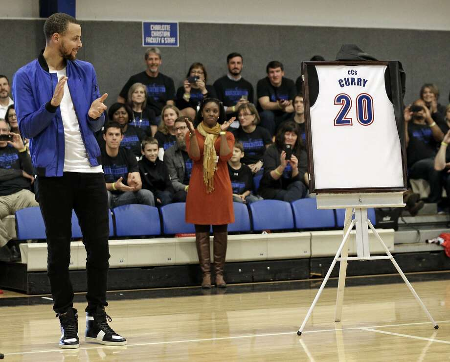 "Golden State Warriors' Stephen Curry looks at a jersey with his name and high school basketball number, during a halftime ceremony at his former high school in Charlotte, N.C., Tuesday, Jan. 24, 2017. Curry is being honored during his return home to Charlotte. His high school retired his number while Davidson College will honor him by renaming a section of its arena ""Section 30."" (AP Photo/Chuck Burton) Photo: Chuck Burton, Associated Press"