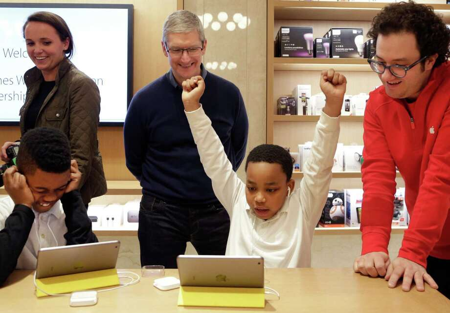 FILE - In this Wednesday, Dec. 9, 2015, file photo, Jaysean Erby raises his hands as he solves a coding problem as Apple CEO Tim Cook watches from behind at an Apple Store, in New York, as Apple hosted Hour of Code events around the world as part of Computer Science Education Week. Despite loudly touted efforts, the tech industry is making very little progress in diversifying its workforce, especially in technical and leadership positions. Companies are spending a lot of time and money on improving diversity, from outreach at high schools and historically black colleges to internship and mentoring programs to sponsorships for coding boot camps to bias training and support groups. So far, to little avail. (AP Photo/Mark Lennihan, File) Photo: Mark Lennihan, STF / Copyright 2016 The Associated Press. All rights reserved.