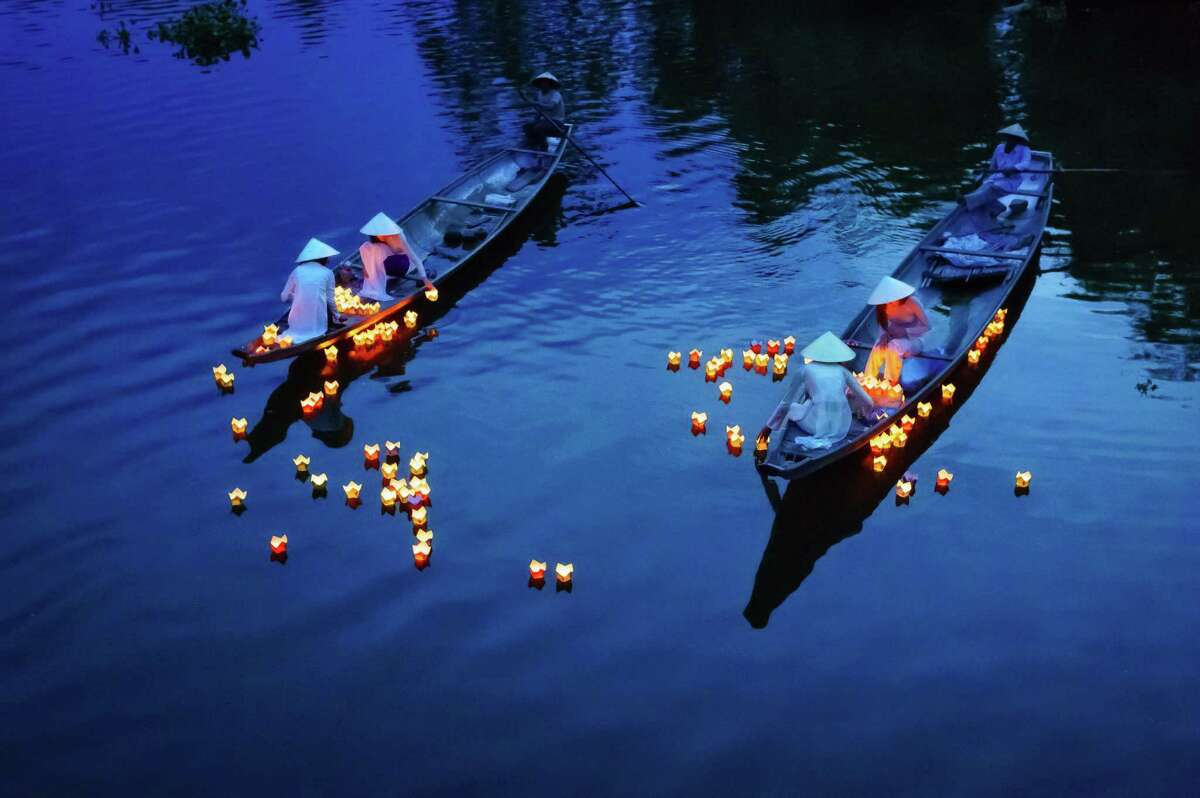 The girls in Ao Dai dresses (traditional dresses) in Hue city (Central of Vietnam) were releasing the floating candles on the river to pray for the dead people. It's a traditional manners of Vietnamese people.