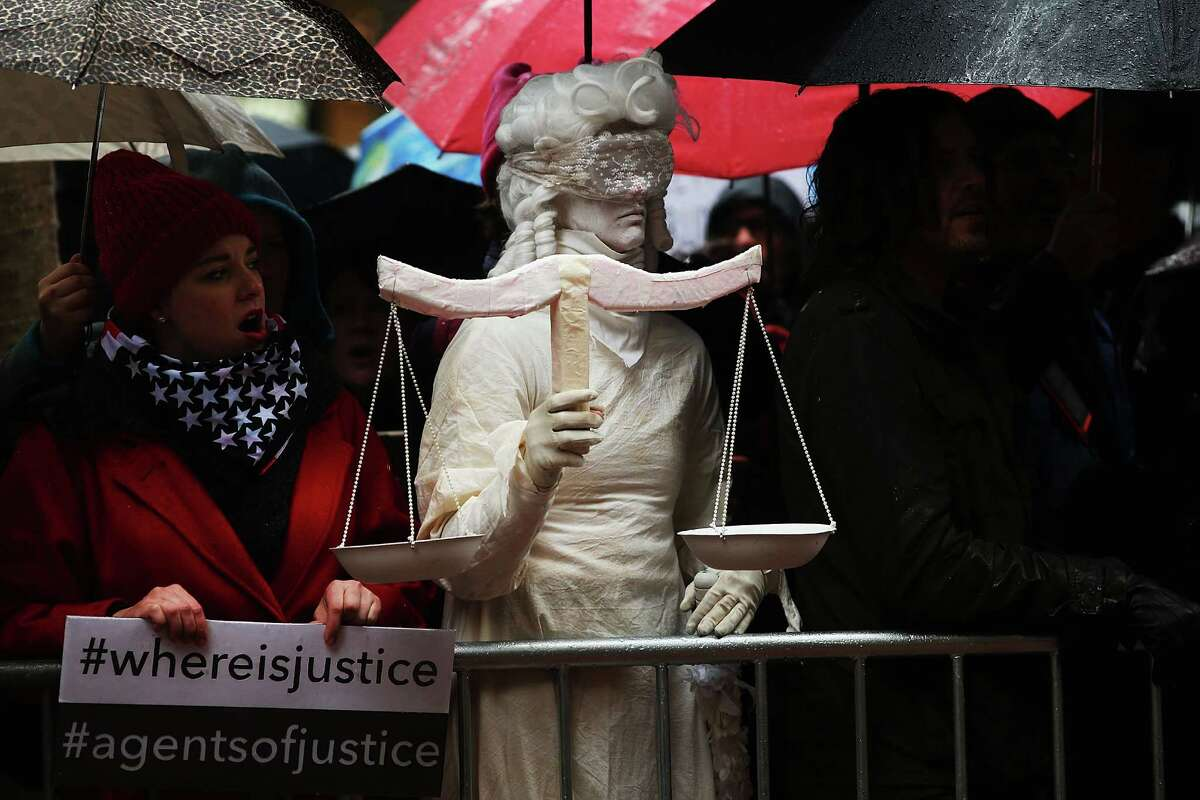 NEW YORK, NY - JANUARY 24: A woman dressed as Lady Justice joins over 100 protesters, many of them women, at a rally in heavy rain outside of the offices of Democratic Senators Chuck Schumer and Kirsten Gillibrand to demand that they hold up the nomination process of President Donald Trump's cabinet choices on January 24, 2017 in New York City. Numerous Trump nominees are being voted on by the Senate this week. (Photo by Spencer Platt/Getty Images) ORG XMIT: 694892623