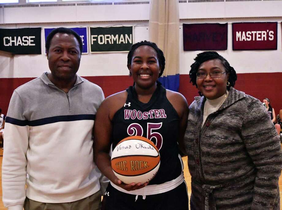 Wooster girls basketball player Venus Okwuka is joined by her parents after breaking the school's all-time scoring record during a game at the Forever Young Gymnasium in Danbury on Jan. 21, 2017. Photo: Contributed Photo / Contributed Photo