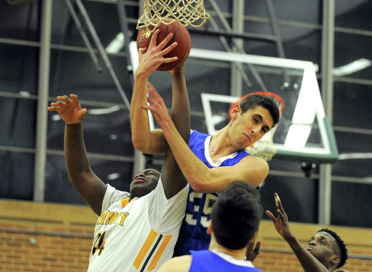 Trinity Timothy Val and Ludlowe Frank Lumaj fight for a rebound in an FCIAC boys basketball game at Trinity Catholic High School's Walsh Court in Stamford, Conn. on Jan. 24, 2017.