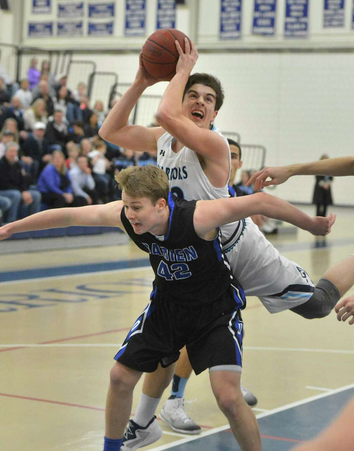 Wilton's Kyle Shifrin shoots over the back of Darien's Andrew Darby during Tuesday's game at Wilton High School. The Warriors stayed undefeated and improved their record to 10-0.