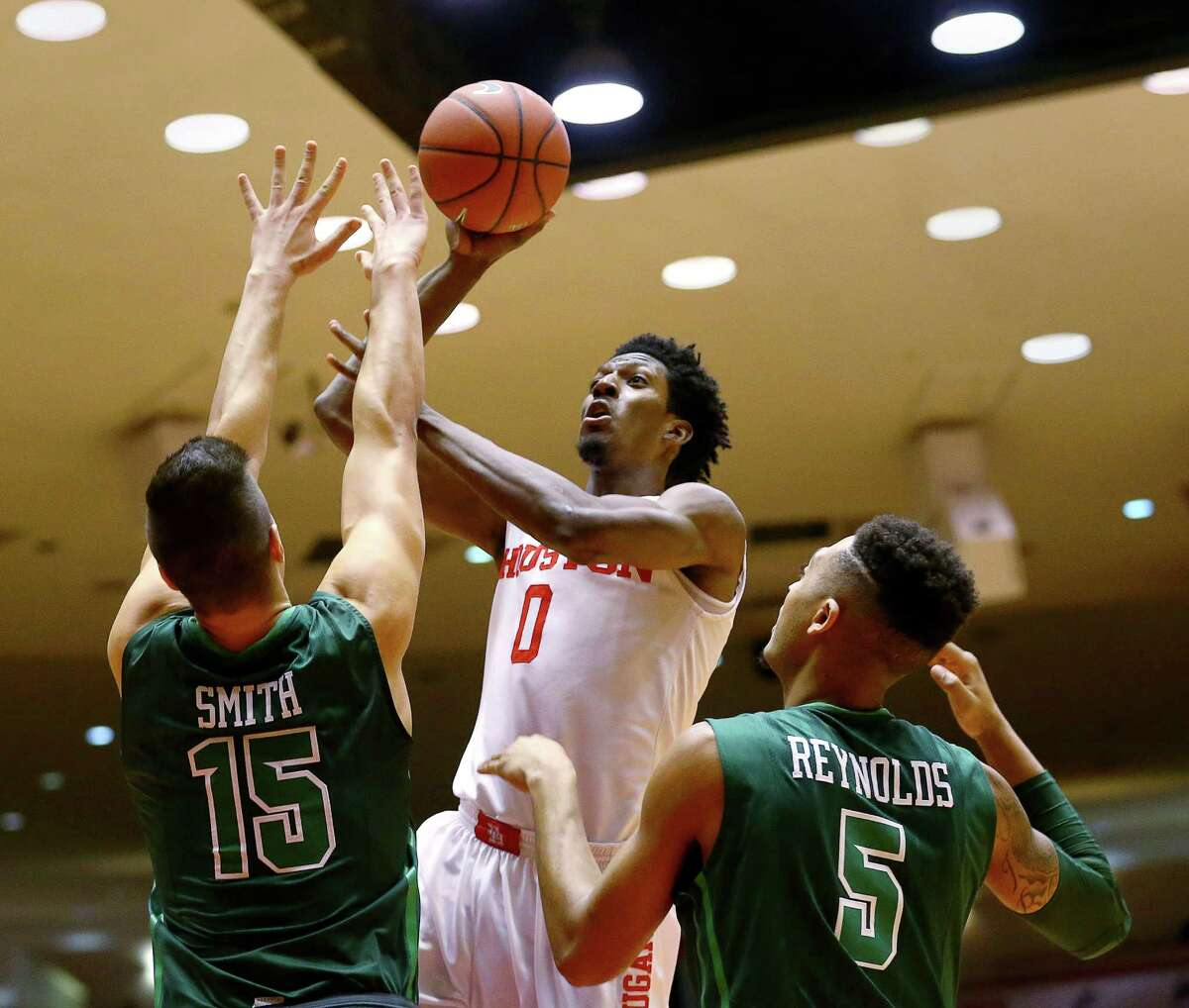 Houston Cougars forward Danrad Knowles (0) shoots over Tulane Green Wave center Ryan Smith (15) and guard Cameron Reynolds (5) during the first half of an NCAA basketball game at Hofheinz Pavillion, Tuesday, Jan. 24, 2017, in Houston.