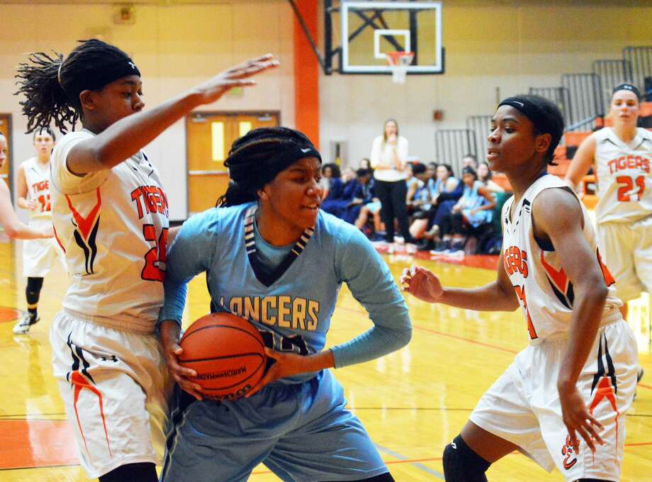 Edwardsville's Criste'on Waters, left, and Myriah Noodel-Haywood, right, guard a Belleville East player during second-half action Tuesday inside Lucco-Jackson Gymnasium.