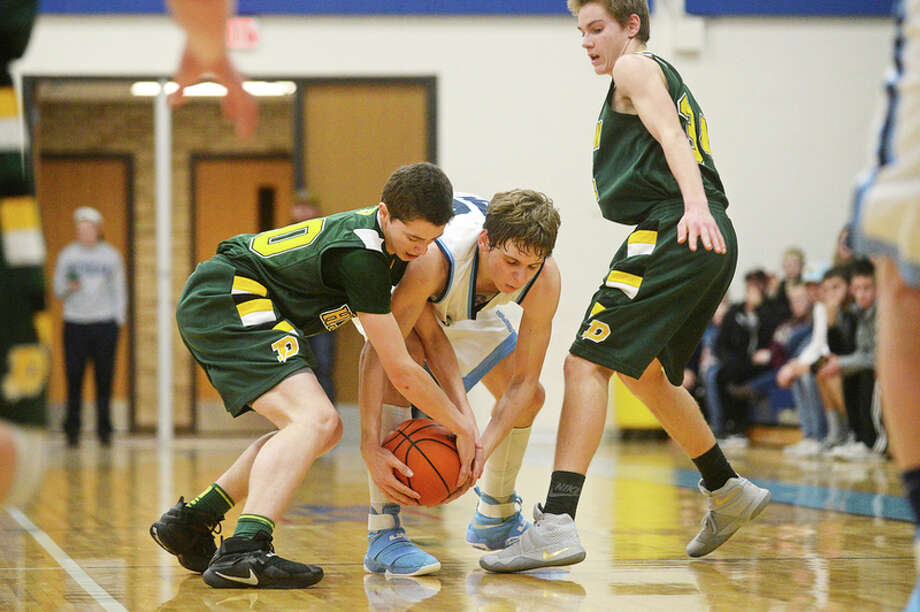 ERIN KIRKLAND | ekirkland@mdn.net Dow's Mitchell Hayes, left, and Meridian's Lucas Lueder, right, battle for possession of the ball as Dow's Isaac Moolenaar, right, watches on Tuesday at Meridian High School. The Mustangs defeated the Chargers 45-41.