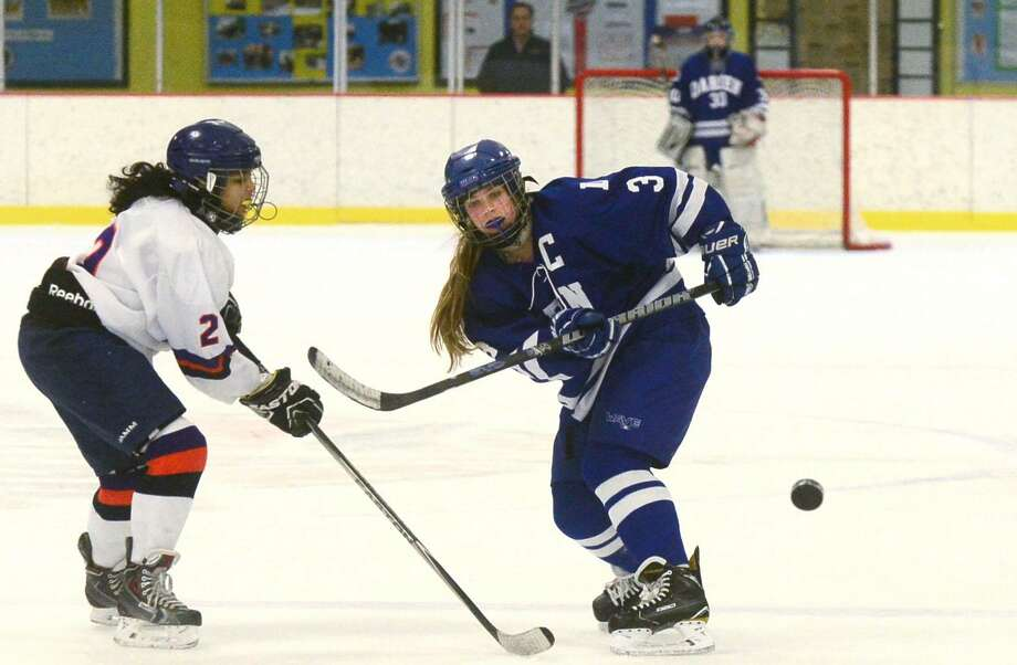 Darien's Courtney Lowe, right, gets the puck past Stamford-Westhill-Staples defender Rachel Menah during their FCIAC girls ice hockey game on Saturday at Terry Connor Rink in Stamford. Darien won 7-0. Photo: Erik Trautmann / Hearst Connecticut Media / Norwalk Hour