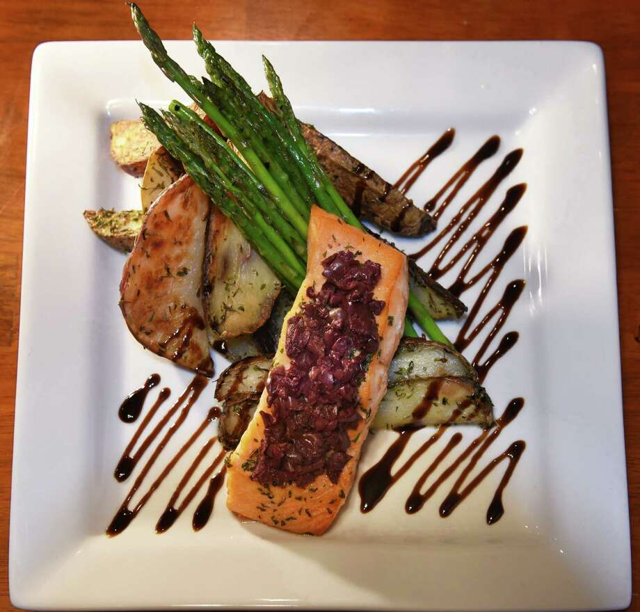 Pan seared salmon topped with tomatoes and Kalamata olives served with vegetables and potatoes du jour at Willows Bistro on Prospect Street Friday Jan. 20, 2017 in Ballston Spa, NY.  (John Carl D'Annibale / Times Union) Photo: John Carl D'Annibale / 20039480A
