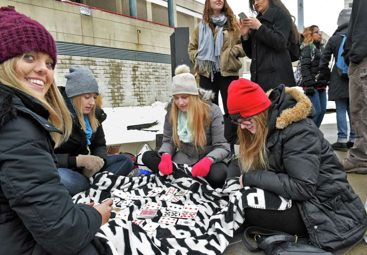 Fans, from left: Morgan Hurley of Buffalo, Kristina Pepe of Buffalo, Stephanie Malangone of Bethlehem and Michala Majore of Albaerta play cards as they wait in line for tonight's Twenty One Pilots concert at the Times Union Center Wednesday Jan. 25, 2017 in Albany, NY. (John Carl D'Annibale / Times Union)