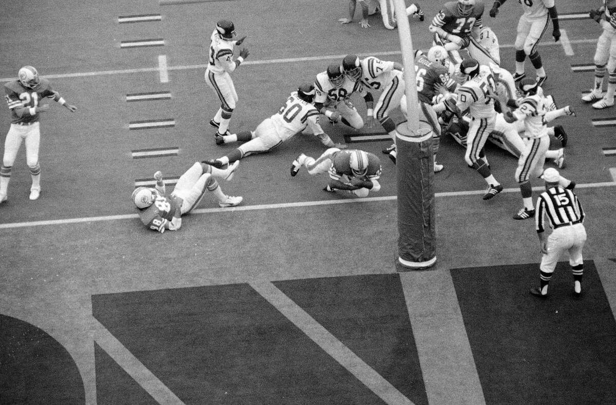 There is a trio of frustrated Viking defenders in his wake as Miami fullback Larry Csonka crashes across to score in third period of Super Bowl VIII Sunday Jan. 13, 1974 in Houston, Tx. Minnesota players are linebackers Roy Winston (60) and Wally Hilgenberg (58) and tackle Bob Lurtsema. The Dolphins won, 24-7. (AP Photo)