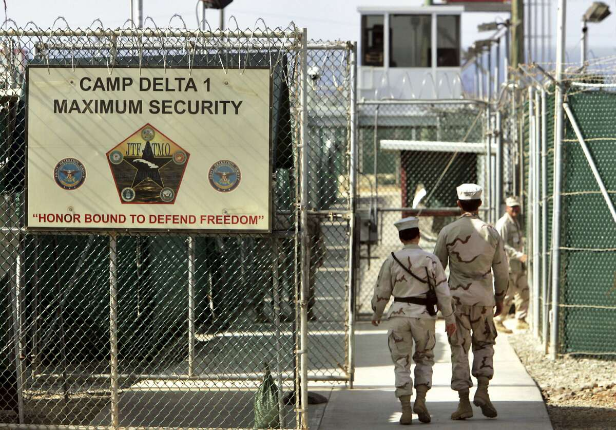 FILE - In this June 27, 2006 file photo, reviewed by a US Department of Defense official, US military guards walk within Camp Delta military-run prison, at the Guantanamo Bay US Naval Base, Cuba. A draft executive order shows President Donald Trump asking for a review of America�s methods for interrogation terror suspects and whether the U.S. should reopen CIA-run �black site� prisons outside the U.S. (AP Photo/Brennan Linsley, file)