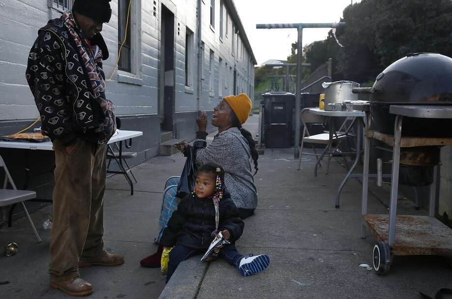 Longtime residents Curtis Cosby (left) and Lisa M. Washington chat while Washington's granddaughter Alanna, 1, sits nearby during a birthday barbecue for Cosby's daughter in the Potrero Terrace and Annex public housing complex. Photo: Leah Millis, The Chronicle