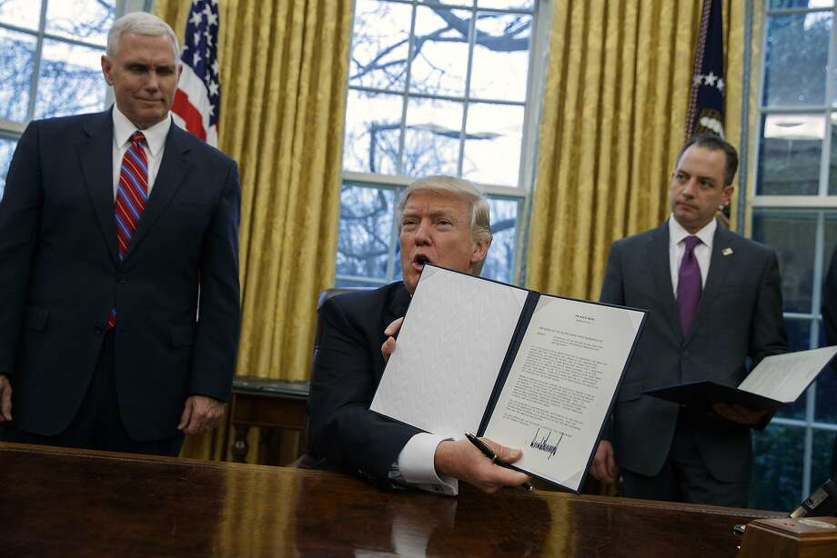 Vice President Mike Pence (left) and White House Chief of Staff Reince Priebus watch as President Trump shows off an executive order to withdraw the U.S. from the 12-nation Trans-Pacific Partnership. Photo: Evan Vucci, Associated Press