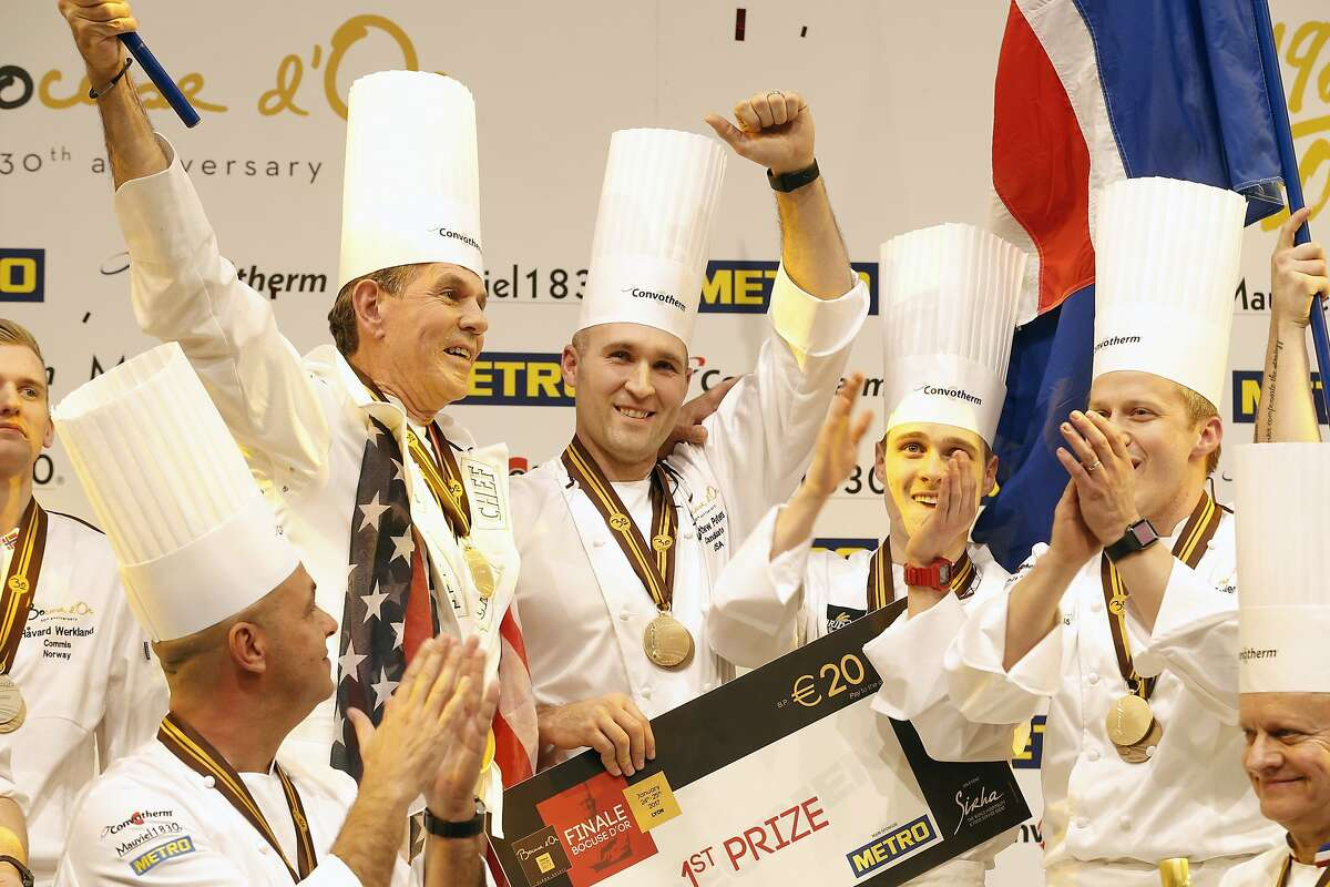 """Mathew Peters of USA, centre, celebrates on the podium with teammates after winning the """"Bocuse d'Or"""" (Golden Bocuse) trophy, in Lyon, central France, Wednesday, Jan. 25, 2017. The contest, a sort of world cup of the cuisine, was started in 1987 by Lyon chef Paul Bocuse to reward young international culinary talents. (AP Photo/Laurent Cipriani)"""
