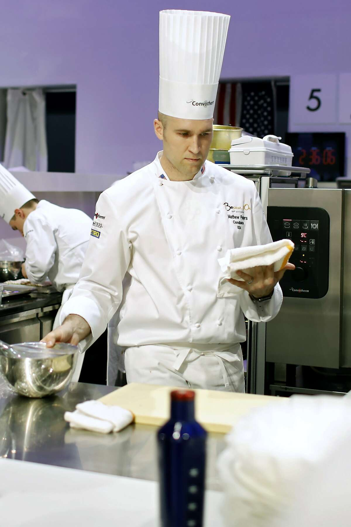 """Mathew Peters, of USA, prepares food during the """"Bocuse d'Or"""" trophy, in Lyon, central France, Wednesday, Jan. 25, 2017. The contest, a sort of world cup of cuisine, was started in 1987 by Lyon chef Paul Bocuse to reward young international culinary talents. (AP Photo/Laurent Cipriani)"""
