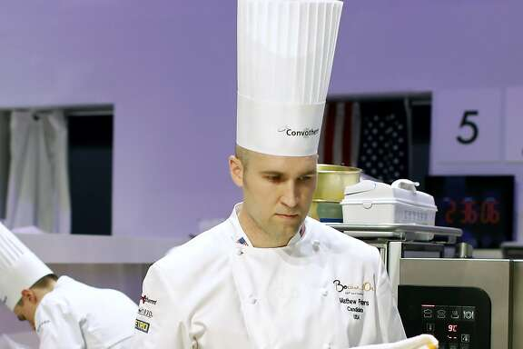"Mathew Peters, of USA, prepares food during the ""Bocuse d'Or"" trophy, in Lyon, central France, Wednesday, Jan. 25, 2017. The contest, a sort of world cup of cuisine, was started in 1987 by Lyon chef Paul Bocuse to reward young international culinary talents. (AP Photo/Laurent Cipriani)"
