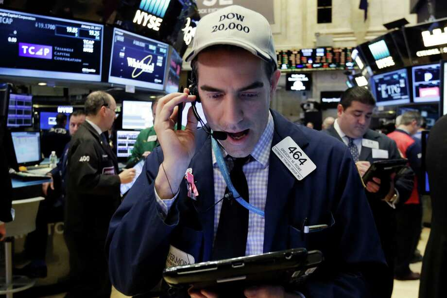 Trader Gregory Rowe wears a Dow 20,000 cap as he works on the floor of the New York Stock Exchange, Wednesday, Jan. 25, 2017. The Dow Jones industrial average is trading over 20,000 points for the first time, the latest milestone in a record-setting drive for the stock market. The market has been marching steadily higher since bottoming out in March 2009 in the aftermath of the financial crisis. (AP Photo/Richard Drew) Photo: Richard Drew, STF / AP